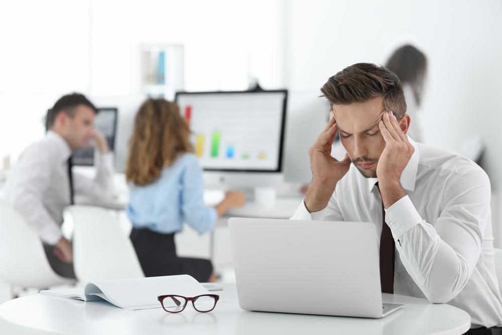 Mann mit Kopfschmerzen am Arbeitsplatz
