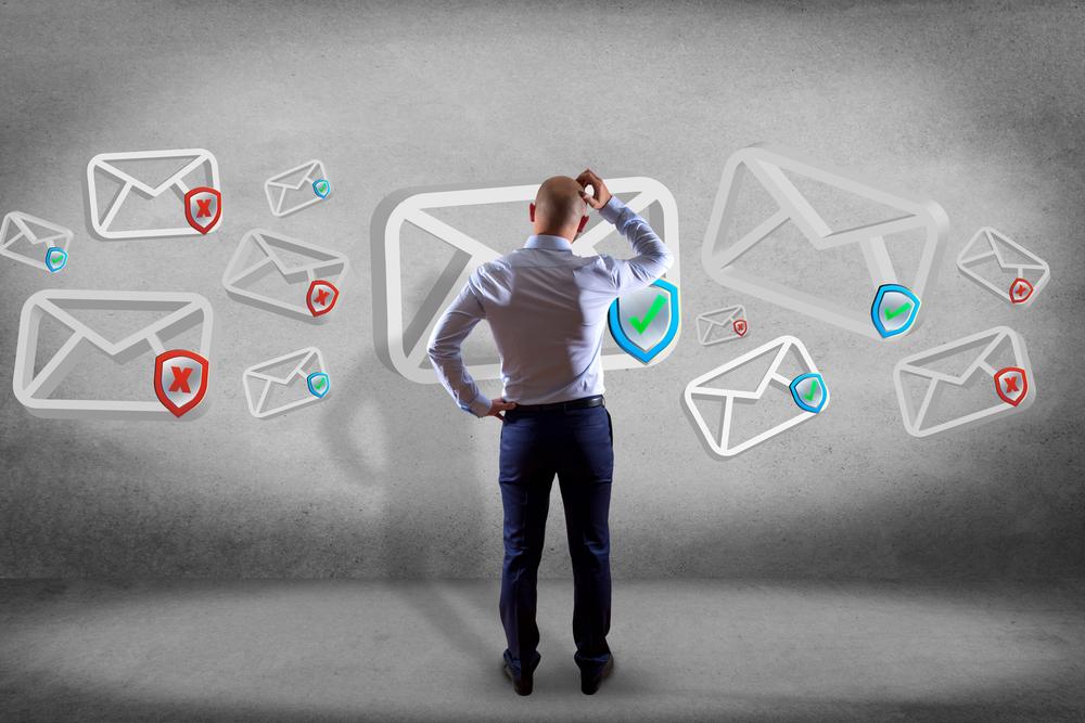 Mann kratzt sich am Kopf und wundert sich über E-Mails